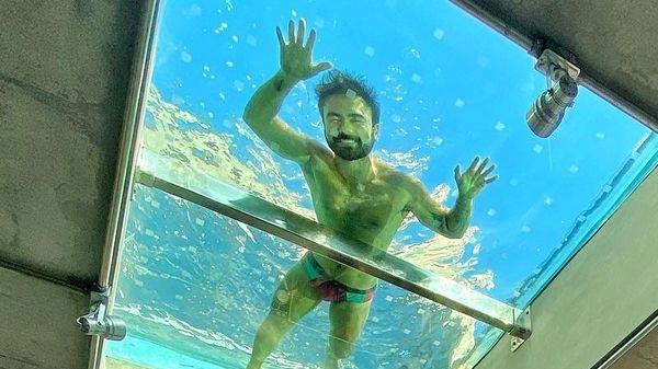 foto de Mauro Souza em sua piscina localizada acima da casa com fundo de vidro